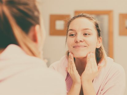 Dry skin in the winter woman cleansing her face and looking in the mirror