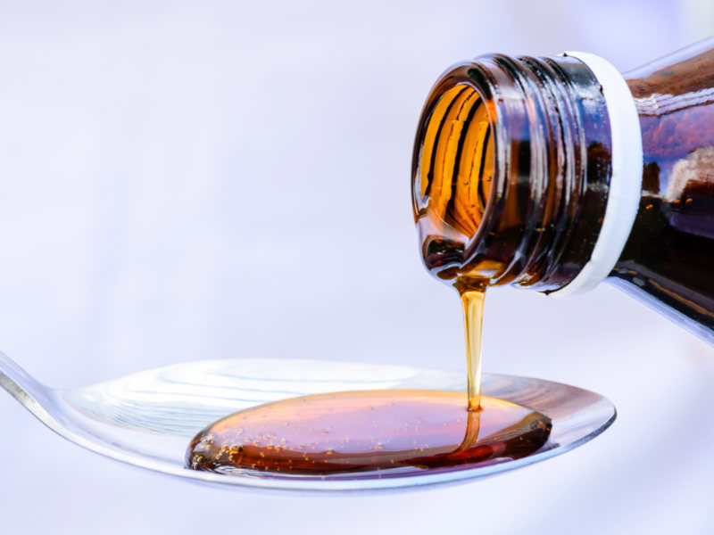 How to Get Rid of the Flu cough syrup being poured onto a spoon