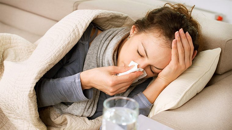 How to Get Rid of the Flu ill woman on couch drying her nose with a tissue