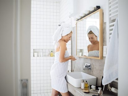 Dry skin in the winter woman wrapped in towel in bathroom