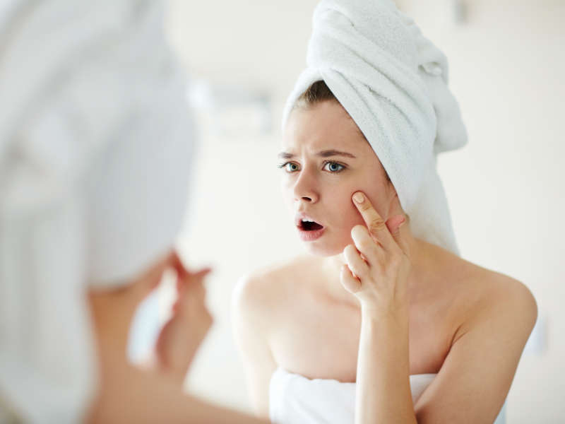 Woman staring in mirror at pimple on her cheek