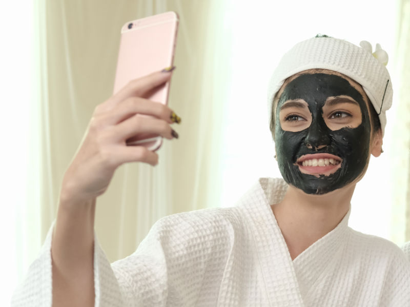 woman with charcoal mask taking a selfie