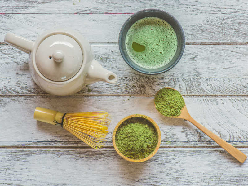 matcha green tea powder with hot water and bamboo whisk