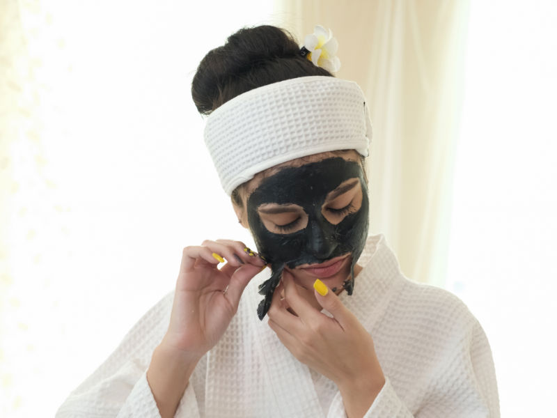 woman peeling charcoal mask off her face
