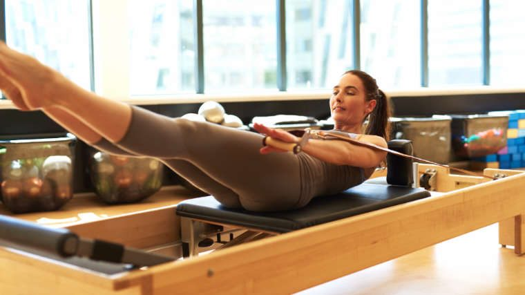 woman on pilates reformer machine
