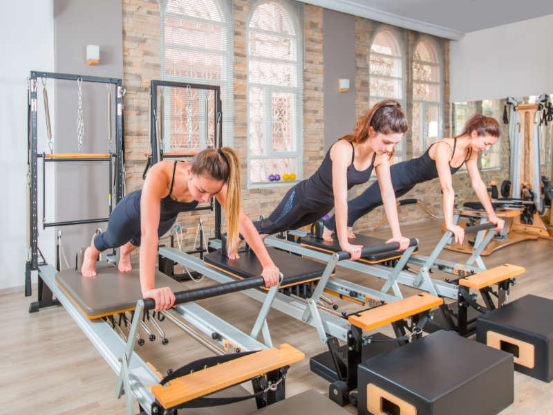women working out on pilates reformer machines