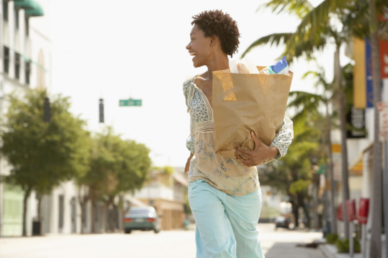 woman carrying grocery bag on street