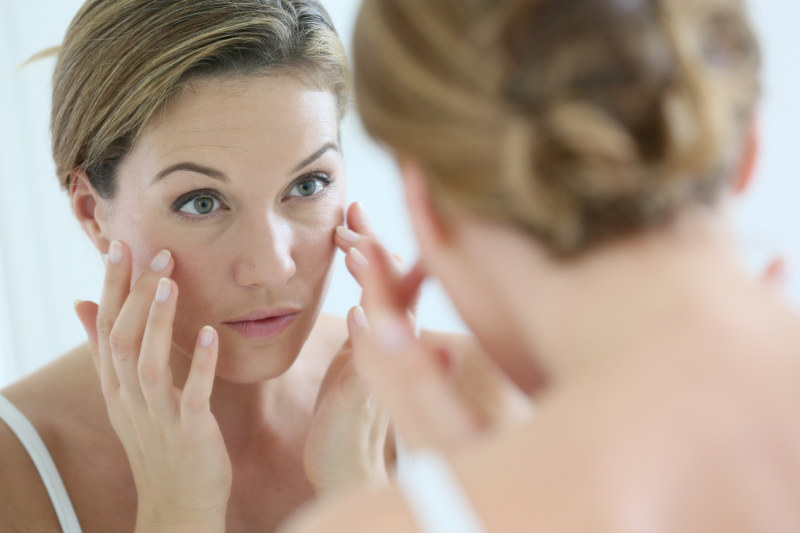 woman looking at her youthful skin in mirror