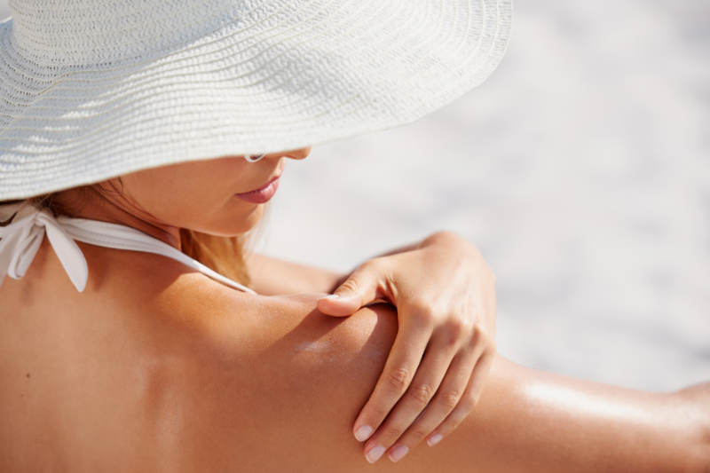 natural sunscreen being applied on shoulder by woman