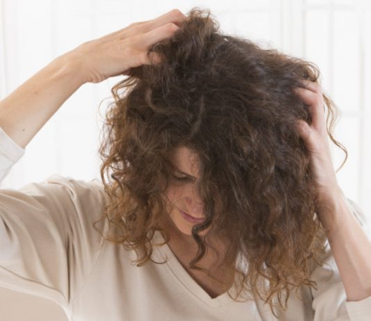 woman scratching her dry scalp