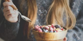 woman with bowl of oatmeal and fruit