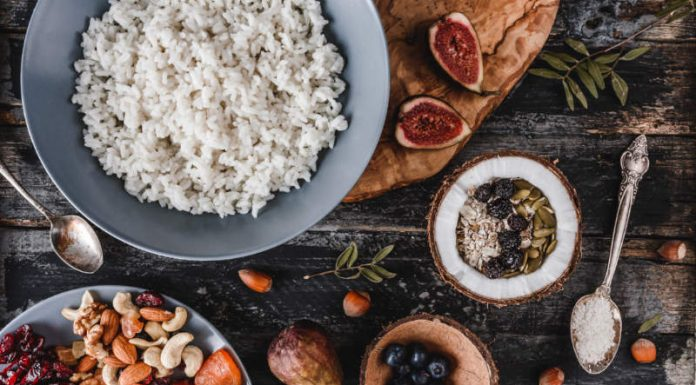 bowl of rice next to dried fruit and nuts