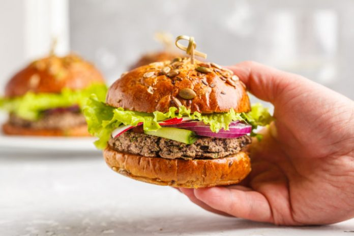 veggie burger in hand