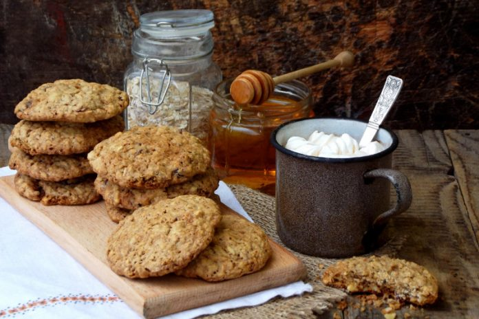 peanut butter oatmeal cookies on a board next to oats and honey