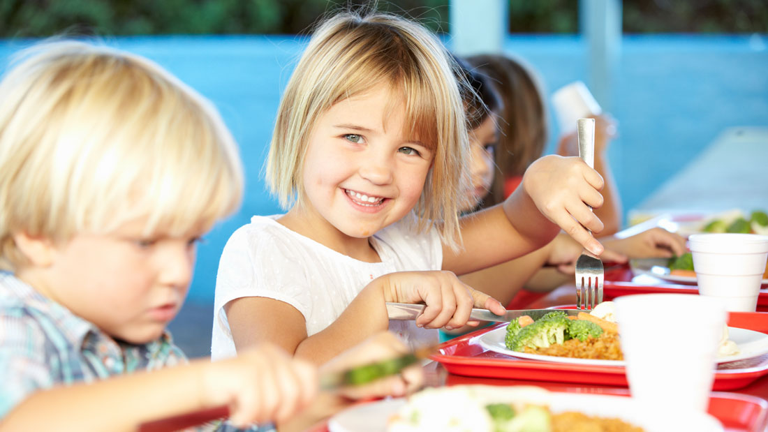 Elementary-Pupils-Enjoying-Healthy-Lunch-In-Cafeteria_141106657