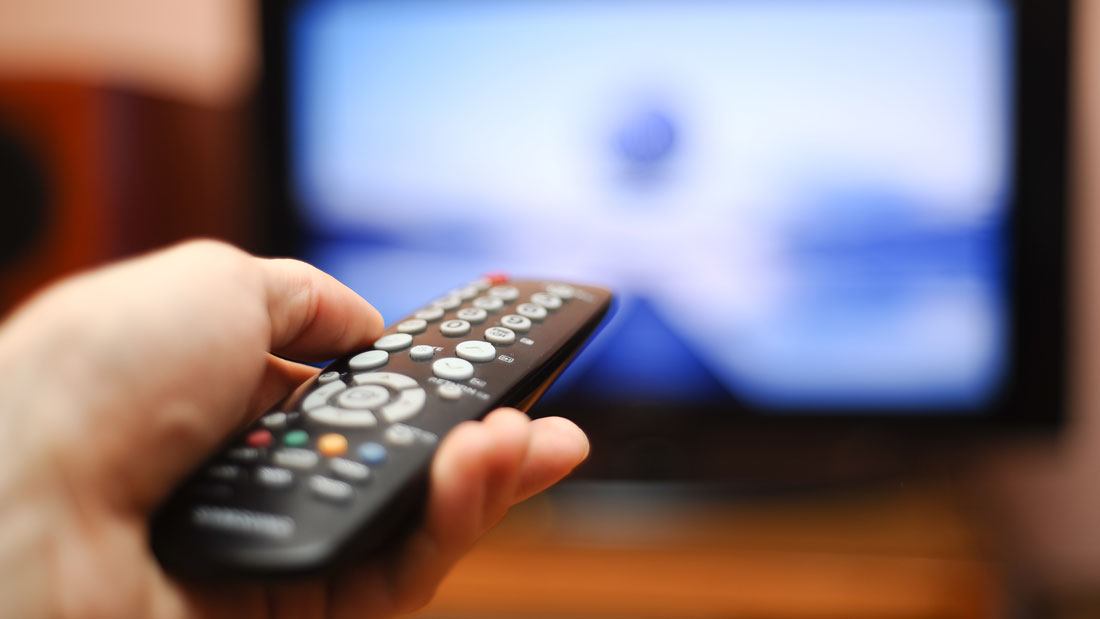 Watching-TV-and-using-remote-controller_163369238