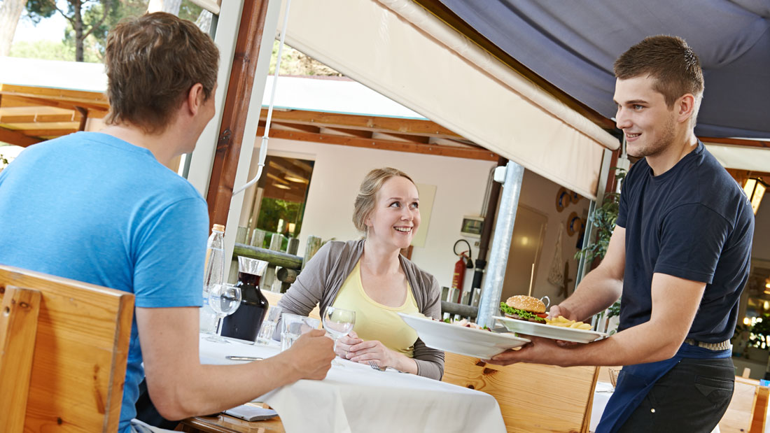 waiter-serving-young-couple-in-restaurant_152548082