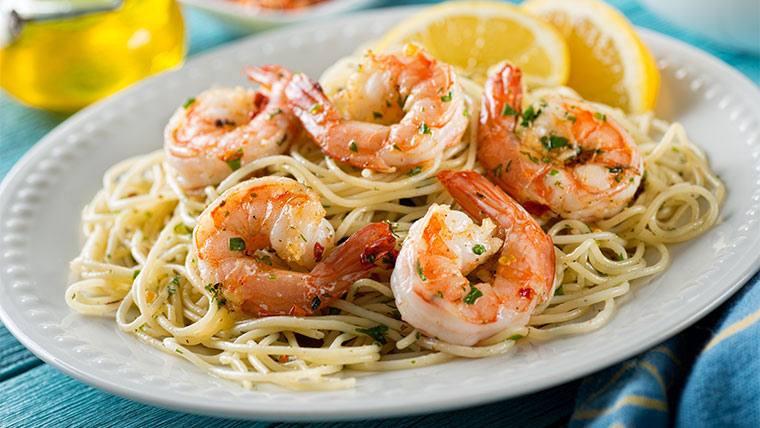 Healthy Shrimp Scampi sitting on top of spaghetti with lemon wedges