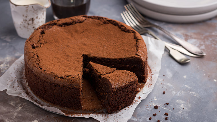 Flourless chocolate cake dusted with cocoa powder with one slice of cake cut out