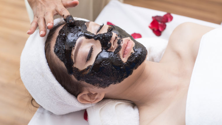 woman getting charcoal mask painted on her face