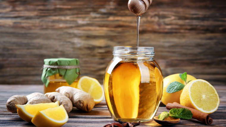 natural remedies on wooden board including jar of honey and mint