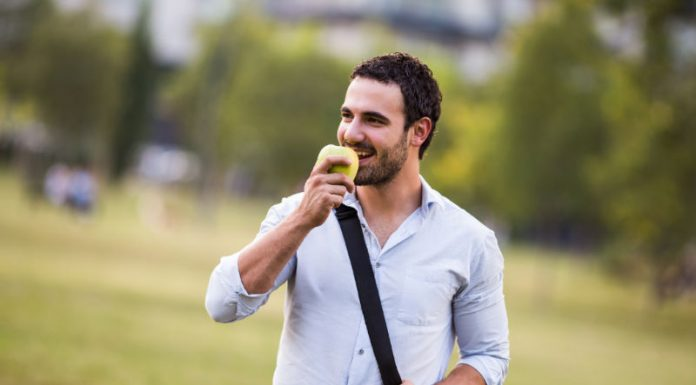 man smiling and eating an apple