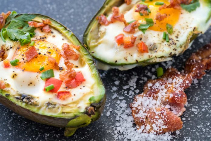 baked eggs in avocado with crumbled bacon