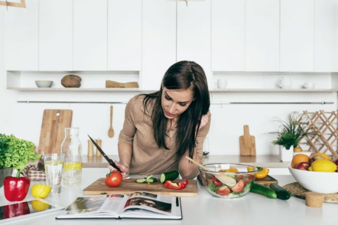 woman using cookbook to prepare healthy meal