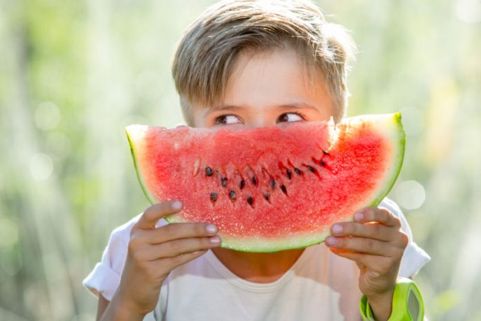 little boy holding up a slice of watermelon
