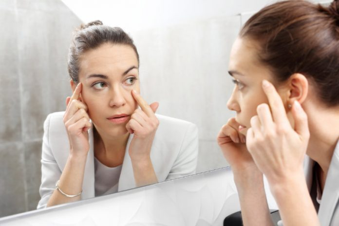 woman staring at her wrinkles in the mirror