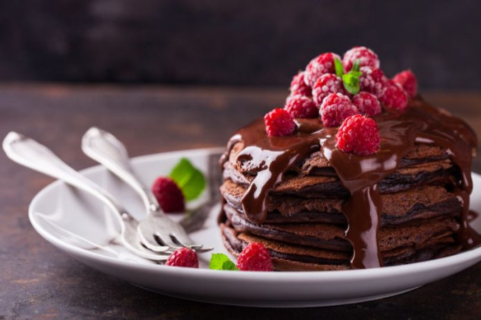 stack of chocolate pancakes with chocolate sauce and berries