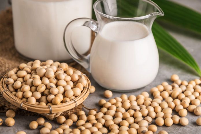 pitcher of soy milk next to soy beans