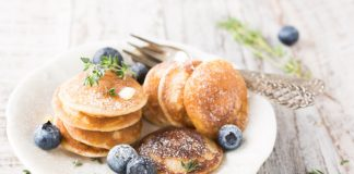 stack of healthy pancakes on a plate with fresh blueberries