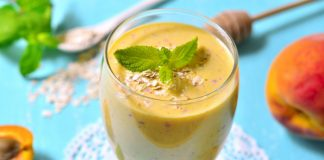 apricot lassi in a cup with fresh mint on top