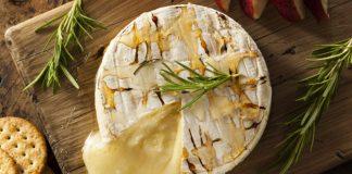 Baked Brie cut open on wooden board