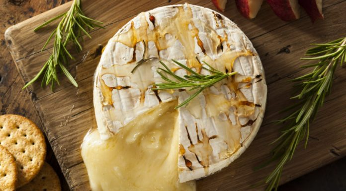 Baked Brie cut open on wooden board