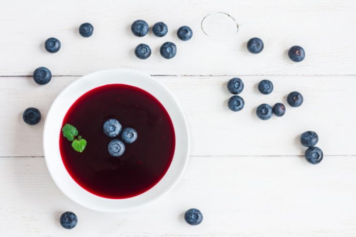 blueberry soup in a bowl with fresh blueberries