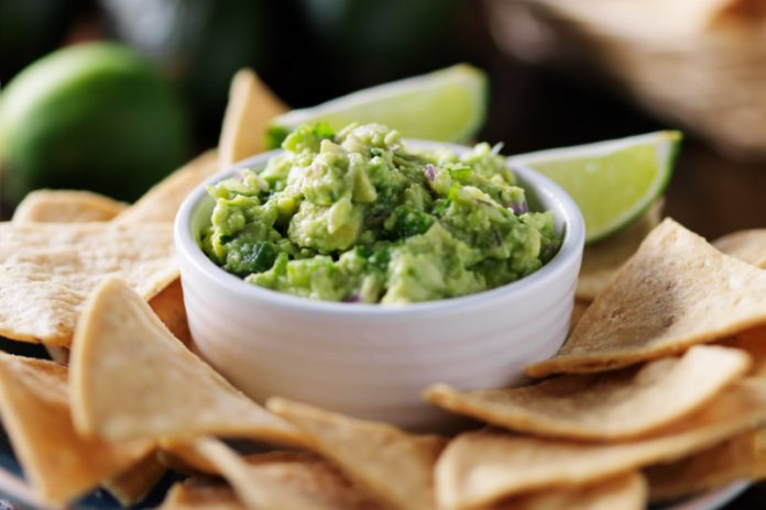 chipotle guacamole in a bowl with tortilla chips