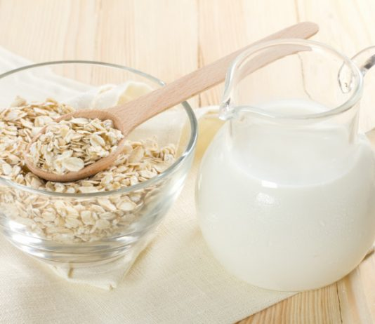 Oat Milk in a pitcher next to a bowl of oats
