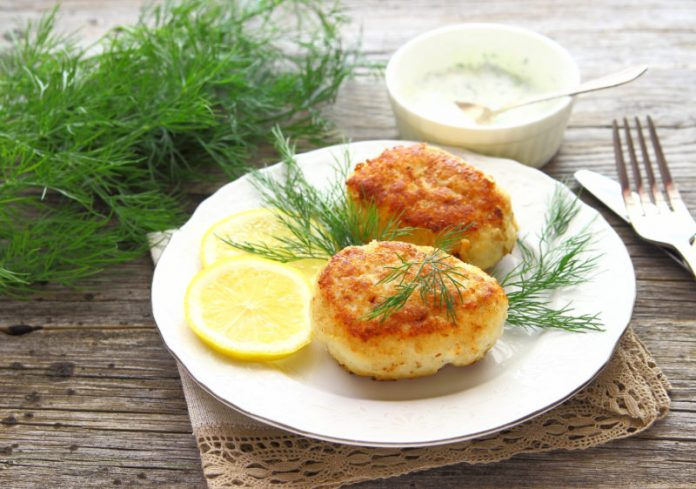 salmon patties on a plate with dill and lemon