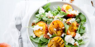 summer salad with peaches and cheese in a bowl
