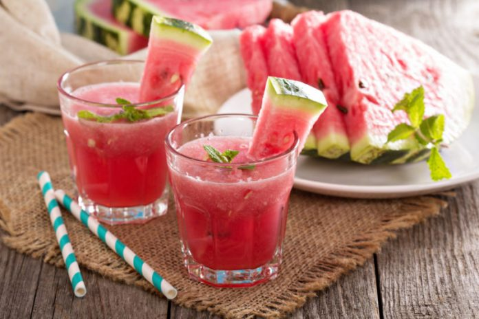 watermelon drink in cups with watermelon slices as garnishes