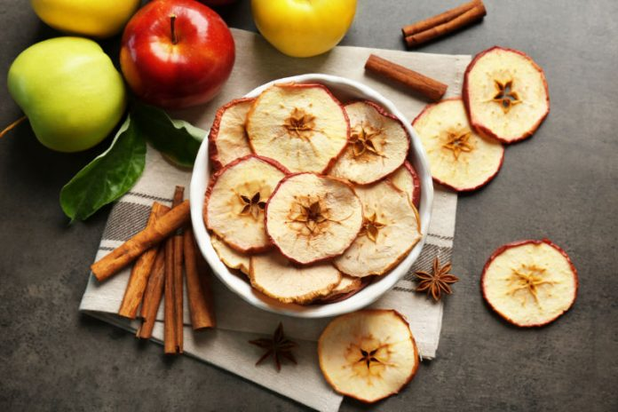 apple chips in a bowl next to cinnamon and fresh apples