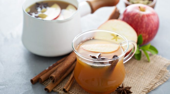 apple cider in a cup with cinnamon sticks and spices