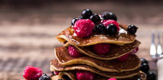 buckwheat pancakes stacked onto a plate with berries and maple syrup
