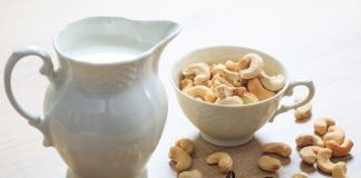 cashew milk in a pitcher with raw cashews