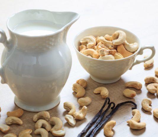 cashew milk in a pitcher with raw cashews