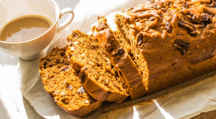 date and walnut loaf sliced next to a cup of tea