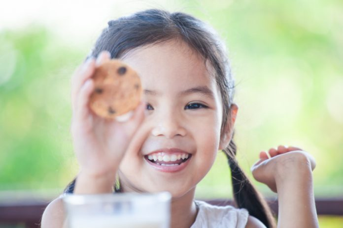 little girl holding a cookie