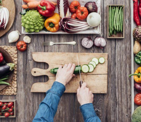 man on vegan diet cutting vegetables on wooden board